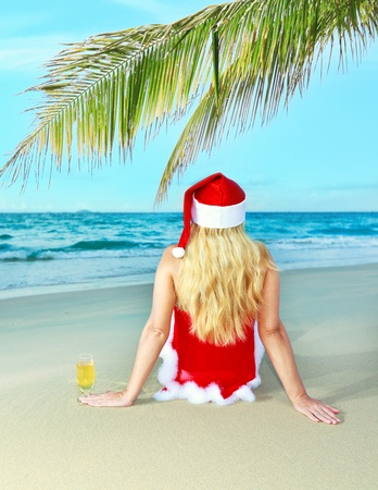Miss Santa sitting near the ocean with glass of wine
