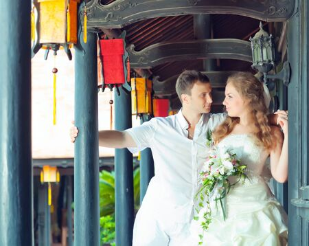 Bride and groom in asian style terrace. photo