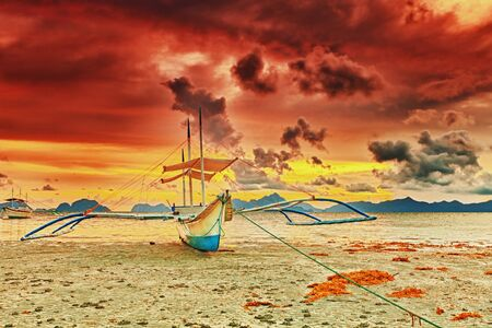 Traditional philippine boat bangka at sunset time photo