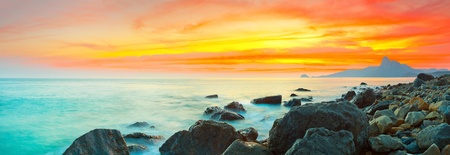 panoramic beach: Sunset over the sea. Stone on the foreground. Panorama