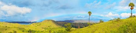 komodo island: Panorama of the Rinca island. Rainbow over savanna