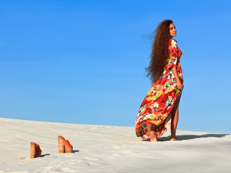 Woman going away in desert photo