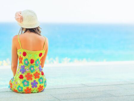 Rear view of woman sitting on the edge of swiming pool Stock Photo - 13442134