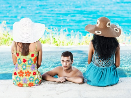 Man and two women on the edge of swimming pool photo