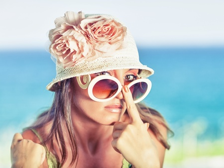 Beautiful woman in sunglasses and hat outdoor