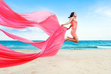 Woman jumping with red scarf photo