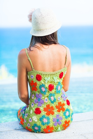 Rear view of woman sitting on the edge of swiming pool photo