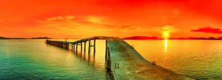 Zonsondergang over de zee. Pier op de voorgrond. Panorama