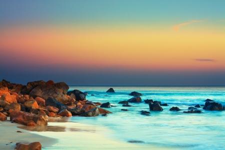 Zonsondergang over de zee. Steen op de voorgrond Stockfoto