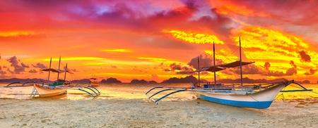 Traditional philippine boat bangka at sunset time photo