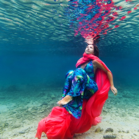 Young beautiful woman in blue dress underwater photo