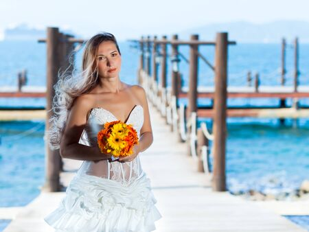 Beautiful bride with wedding bouquet at the pier photo