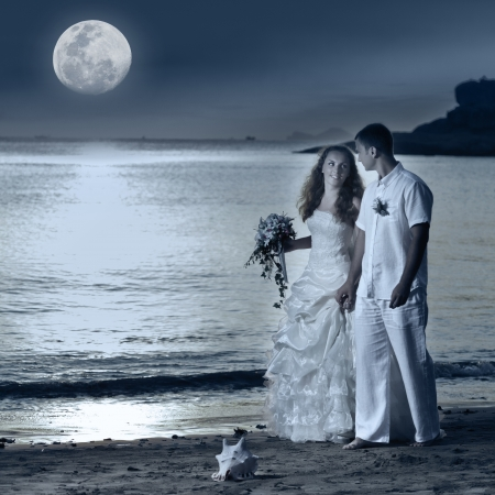 Bride and groom walking on the beach under the moon photo