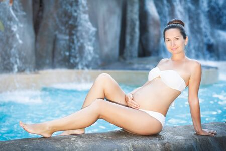 Beautiful pregnant woman in swimming pool photo