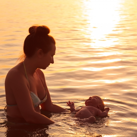 Mother and baby swimming in the sea Foto de archivo
