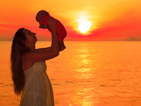 Moeder en baby op het strand bij zonsopgang Stockfoto