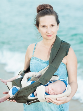 Young mother with baby on the beach photo