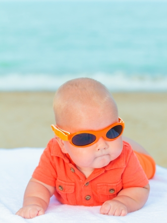 Cute baby laying on the sunbed at the beach photo
