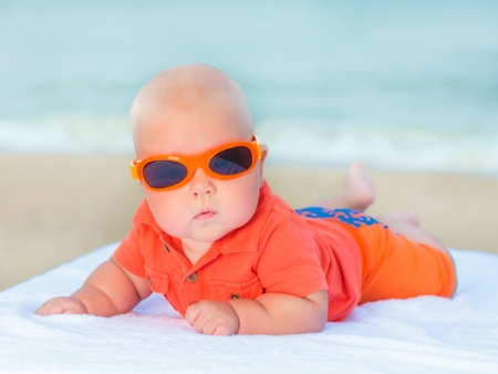 childcare: Cute baby laying on the sunbed at the beach