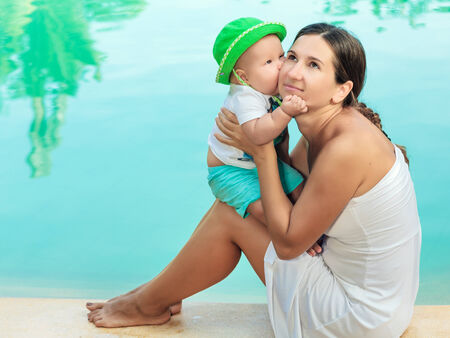 Baby and mother are sitting on the edge of a pool photo