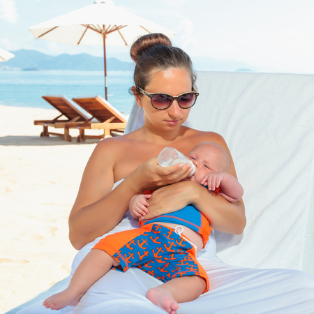 Baby and mother feeding on sunbed photo