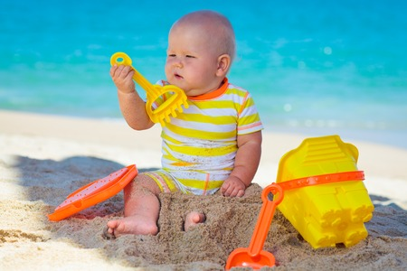 Cute baby on the tropical beach playing toys photo