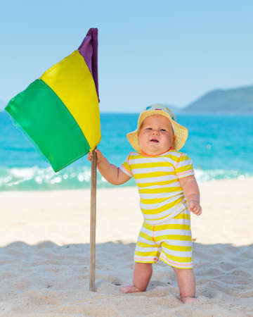 Cute baby on the tropical beach with flag photo