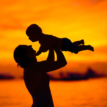 Silhouette of mother and baby at sunset photo