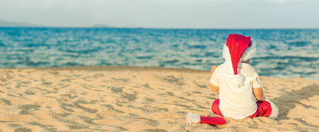 beach panorama: Little Santa on the beach. Panorama Stock Photo
