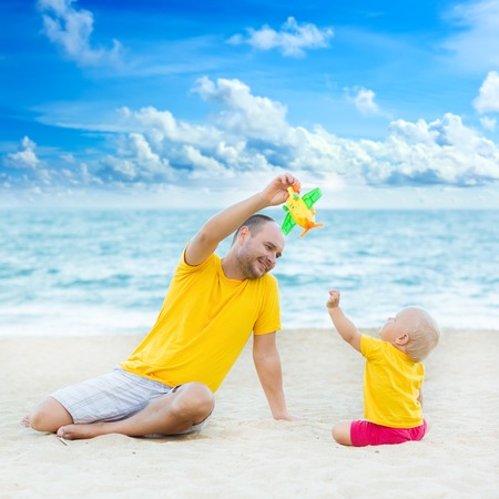 conceptual cute: Baby and father on the tropical beach playing toy plane