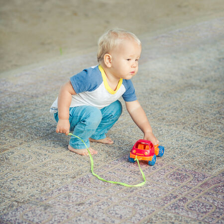 Baby playing with toy car photo