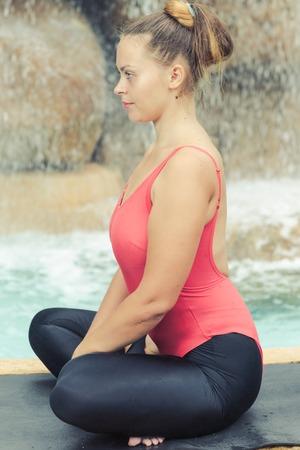 Woman practicing yoga near waterfall. Accomplished Pose. Siddhasana