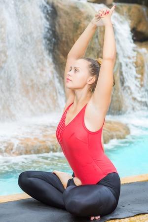 siddhasana: Woman practicing yoga near waterfall. Accomplished Pose. Siddhasana