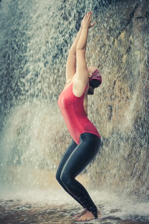 maladroit: Femme pratiquant le yoga pr�s de la cascade. Pose Awkward. Utkatasana