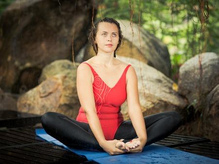 mujer meditando: La mujer se está practicando yoga al aire libre. Pose ángulo Bound. Baddha Konasana