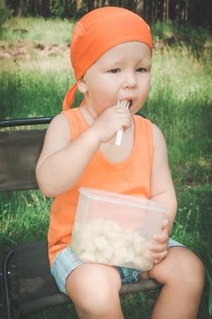 eating fruits: Beb� comer frutas lindo al aire libre Foto de archivo