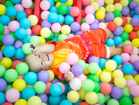 playcentre: Cute kid boy playing with colorful balls Stock Photo
