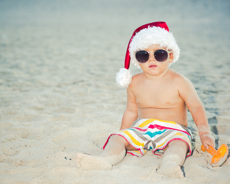 beach happy new year: Cute baby wearing Santa hat on the beach
