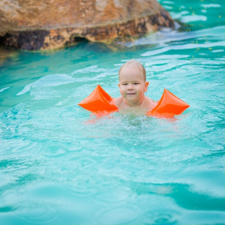 armbands: Baby with armbands in swimming pool Stock Photo