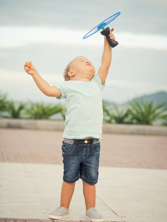 boomerangs: Boy with flying saucer outdoor. Leisure activity
