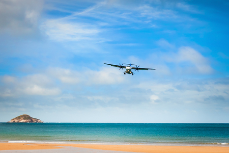 transportaion: Airplane landing over the tropical lagoon at sunny day