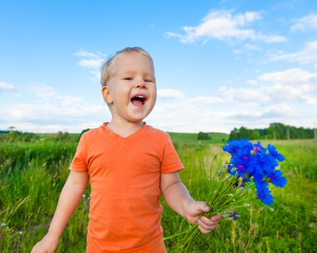 cornflowers: Adorable boy with cornflowers outdoor laughing Stock Photo