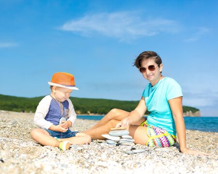 Mother and son making pebble stack near the sea Stock Photo
