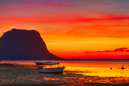 morn: Fishing boat at sunset time. Le Morn Brabant on background. Mauritius.