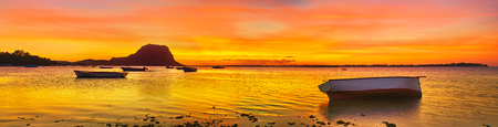 morn: Fishing boat at sunset time. Le Morn Brabant on background. Mauritius. Panorama Stock Photo