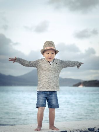 lifestile: Child having fun on the beach at sunset time Stock Photo