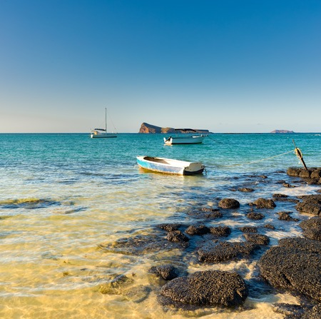 Boats in a sea at day time. Flat island on a background. Mauritius