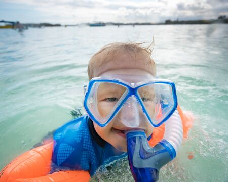 attempt: Boy with armbands, mask and snorkel plays in a sea