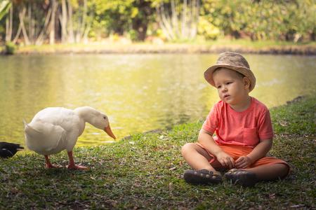 Boy and geese near lake. Mauritius