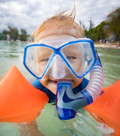 armbands: Boy with armbands, mask and snorkel plays in a sea